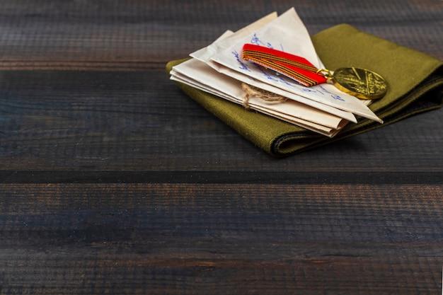 Fondo del día de la victoria - 9 de mayo de 1945. san cartas de primera línea, gorra de guarnición militar y órdenes en el fondo de madera. vista superior, copia espacio para texto