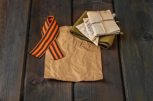 Fondo del día de la victoria. cinta de san jorge, letras de primera línea, gorra de guarnición militar en el fondo de madera.