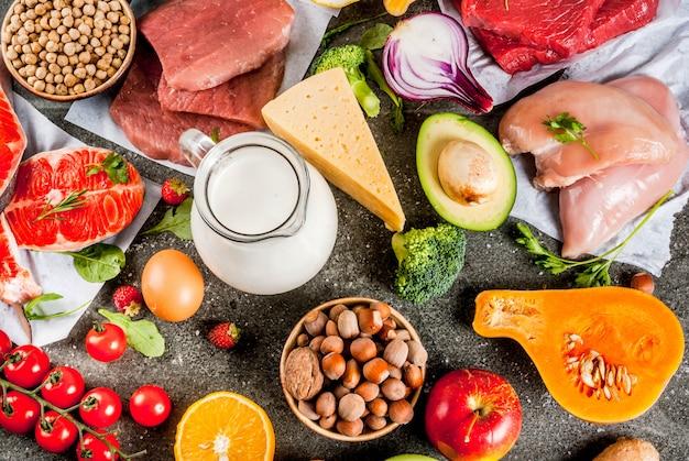 Fondo de dieta saludable ingredientes de alimentos orgánicos superalimentos: carne de res y cerdo filete de pollo salmón pescado frijoles nueces leche huevos frutas verduras mesa de piedra negra