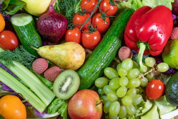 Fondo de diferentes frutas y verduras crudas.