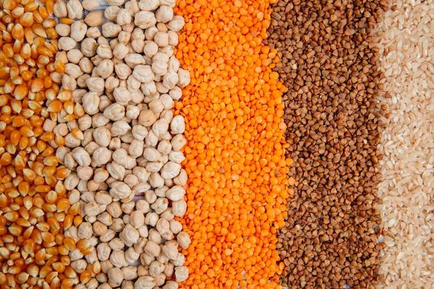 Fondo de diferentes tipos de granos de maíz, garbanzos, lentejas rojas, trigo sarraceno y arroz vista superior