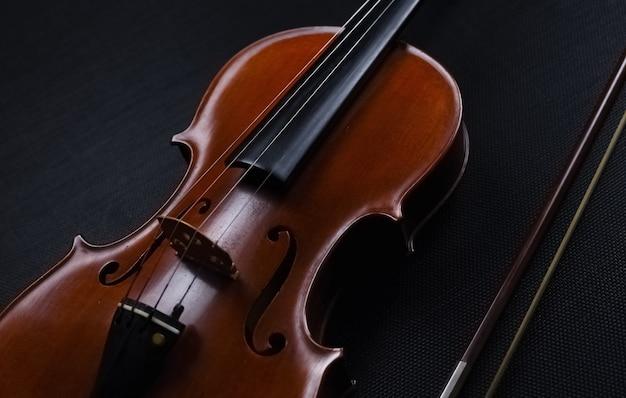 El fondo de diseño de arte abstracto del violín de madera puesto en el fondo, muestra el lado frontal del instrumento de cuerda, sobre fondo de lienzo negro