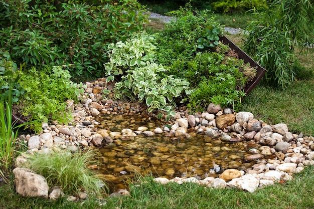 Fondo de diseño de jardines. paisajismo en parque con estanque decorativo.