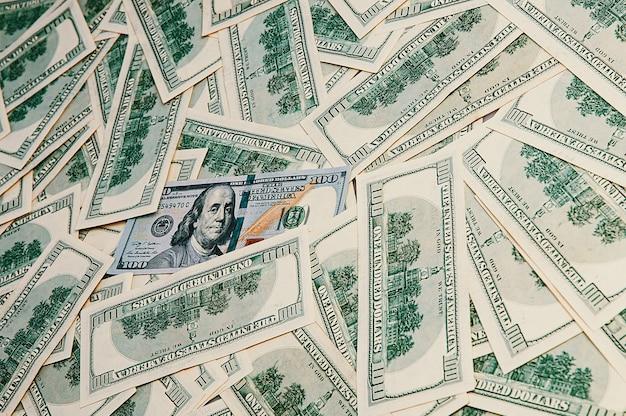 Fondo de dólares. billetes de cien dólares estadounidenses se encuentran esparcidos por el fondo.