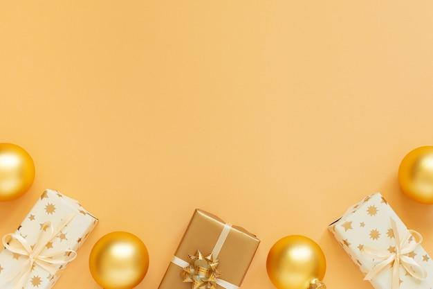 Fondo dorado con cajas de regalo y bolas de navidad