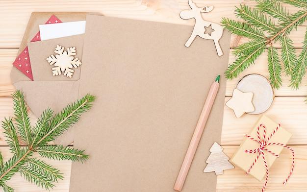 Fondo ecológico navideño con hoja de papel, lápiz, caja de regalo, ramas de abeto.