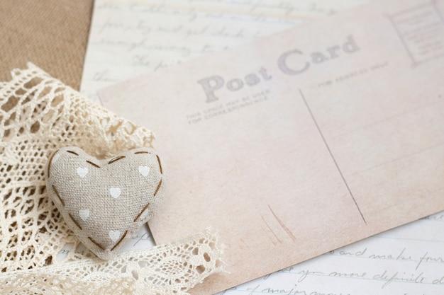 Fondo elegante lamentable con carta manuscrita, postal y corazón de tela