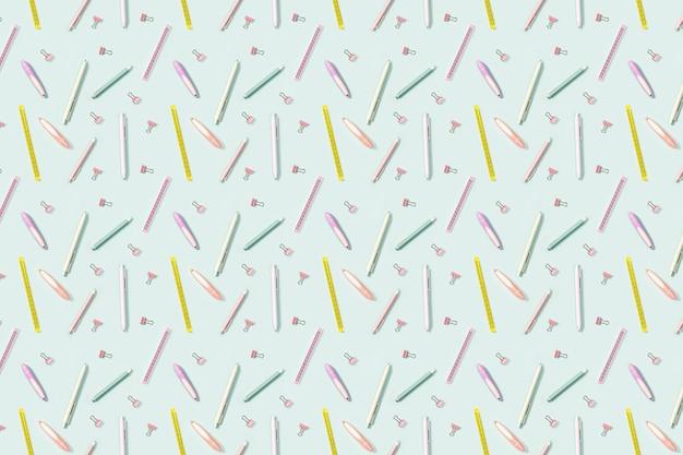 Fondo escolar con patrón de material de oficina, lápices de colores, bolígrafos, puler, marcadores y clips metálicos.