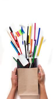 Fondo escolar, útiles escolares, herramientas de escritura en una bolsa de kraft