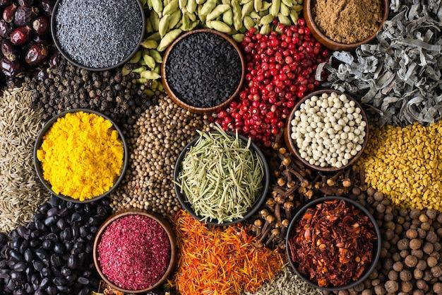 Fondo de especias y hierbas. los diferentes condimentos están esparcidos en color.