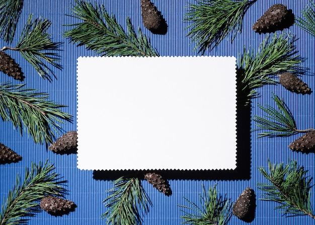 Fondo de felices fiestas con espacio de copia de texto. hoja de papel de nota blanca sobre azul. decoración de conos y ramas de pino