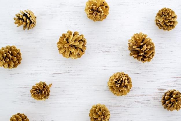Fondo feliz navidad - patrón de conos de pino color oro sobre fondo blanco.