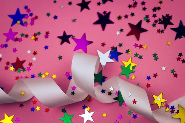 Fondo festivo con cinta de raso y estrellas.
