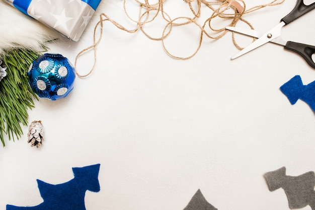 Fondo festivo de la decoración navideña. fieltro abeto, bola de adorno, rama de pino y tijeras con cuerda, vista superior y espacio de copia. preparación de vacaciones, concepto de decoración del hogar y restaurante.