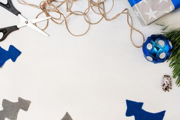 Fondo festivo de decoración de regalo de navidad. fieltro abeto, bola de adorno, caja de regalo y tijeras con cuerda, vista superior y espacio de copia. preparación de vacaciones, concepto de decoración del hogar y restaurante.