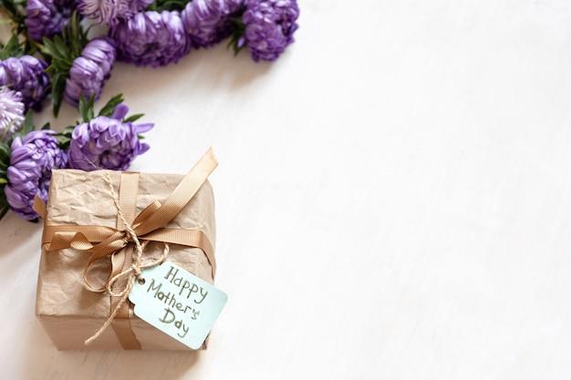 Fondo festivo del día de las madres con caja de regalo y flores de crisantemo frescas sobre fondo blanco, espacio de copia.