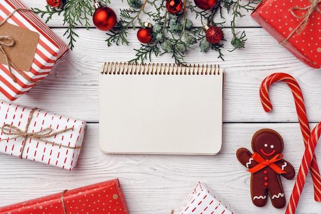 Fondo festivo de invierno con hombre de jengibre y bastones de caramelo sobre tabla de madera blanca, espacio de copia l