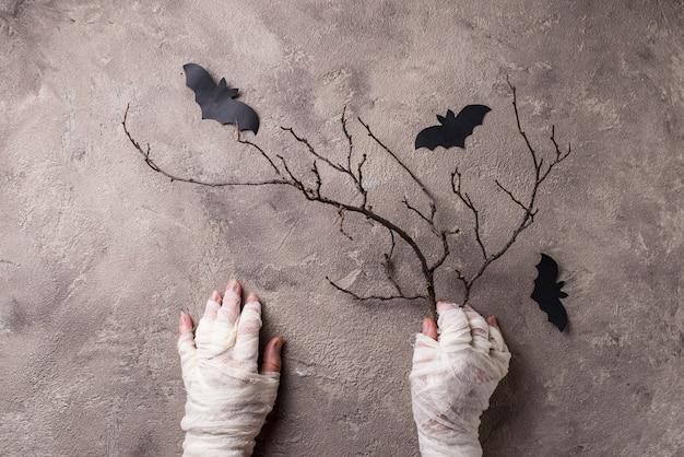 Fondo festivo de miedo de halloween con manos de momia y murciélago