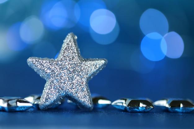 Fondo festivo de navidad, estrella de plata en azul
