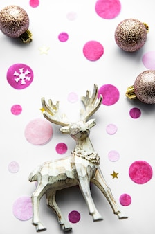 Fondo festivo de navidad con hermosos ciervos, bolas doradas y confeti sobre fondo blanco.