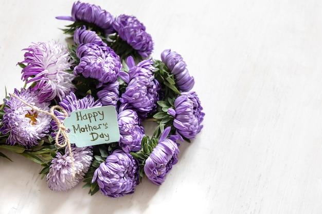 Fondo festivo con un ramo de crisantemos azules y una tarjeta de felicitación con un deseo de un feliz día de la madre sobre un fondo blanco, espacio de copia.