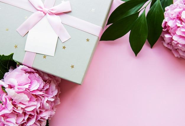 Fondo festivo para una tarjeta de felicitación con una caja de regalo plateada con un lazo y flores de hortensia en colores rosados