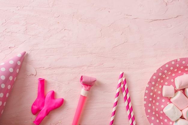 Fondo de fiesta de cumpleaños, borde de confeti, dulces, piruletas y regalo en superficie rosa