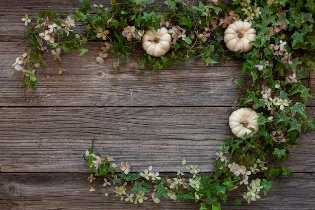 Fondo floral con hiedra verde, flores de hortensia y calabazas decorativas blancas.