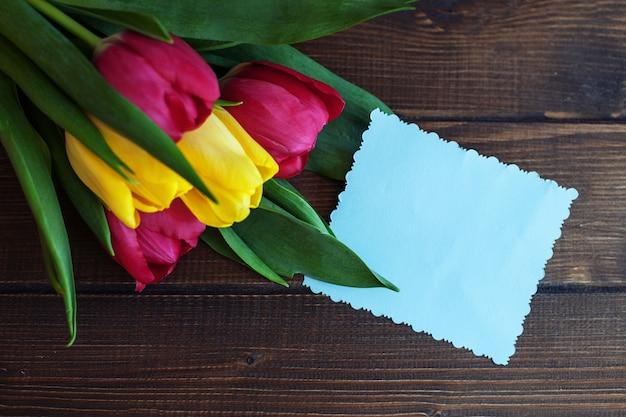 Fondo con flores y una tarjeta de felicitación.