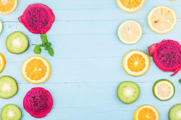 Fondo de frutas. fruta fresca colorida en tablero de madera azul. naranja, fruta del dragón, limón, endecha plana, vista superior,