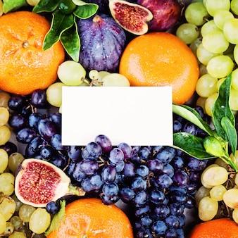 Fondo de frutas con tarjeta de presentación en blanco uva higos ciruela y mandarinas frutas