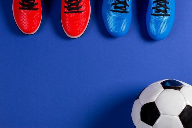 Fondo de fútbol soccer. vista superior del balón de fútbol y dos pares de zapatos deportivos de fútbol sobre fondo azul.