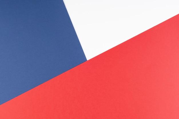 Fondo geométrico abstracto en colores azul, blanco y rojo.