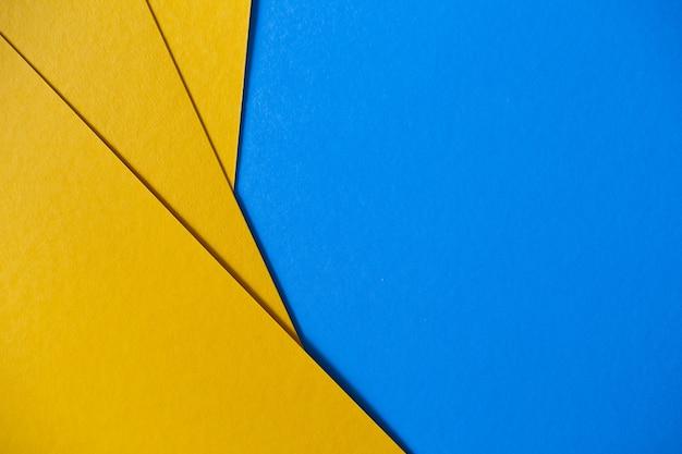 Fondo geométrico coloreado de la textura del papel azul y amarillo