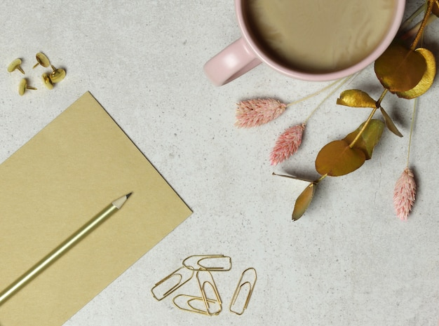 Fondo de granito con notas artesanales, lápiz dorado, clips de papel, taza de café