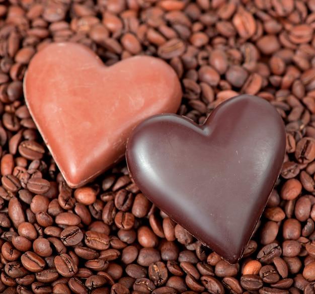 Fondo de granos de café y corazón con caramelos en forma de corazón
