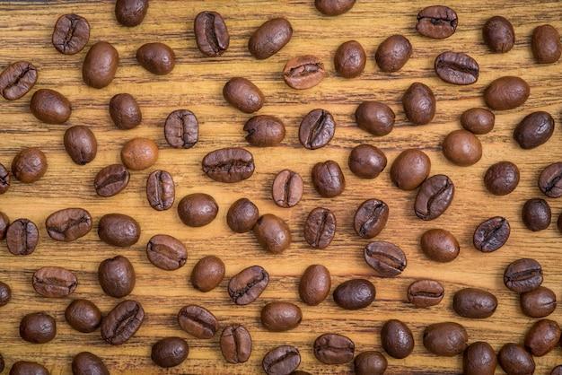 El fondo de los granos de café tostados es marrón sobre tablas de madera.