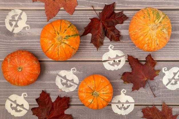 Fondo de halloween de pequeñas calabazas maduras, hojas de arce caídas y estarcido