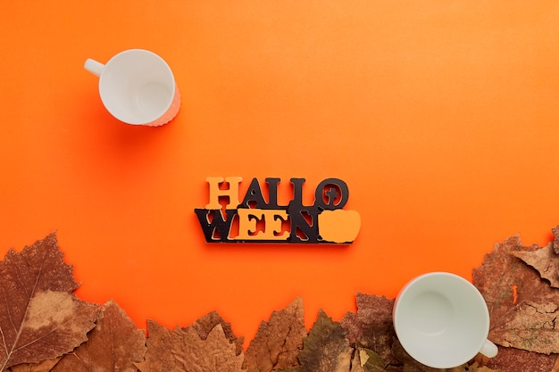 Fondo de halloween, taza en blanco y hojas secas en naranja