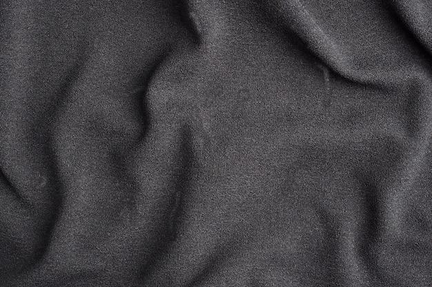 El fondo está hecho de material textil negro, la textura de una prenda de vestir.