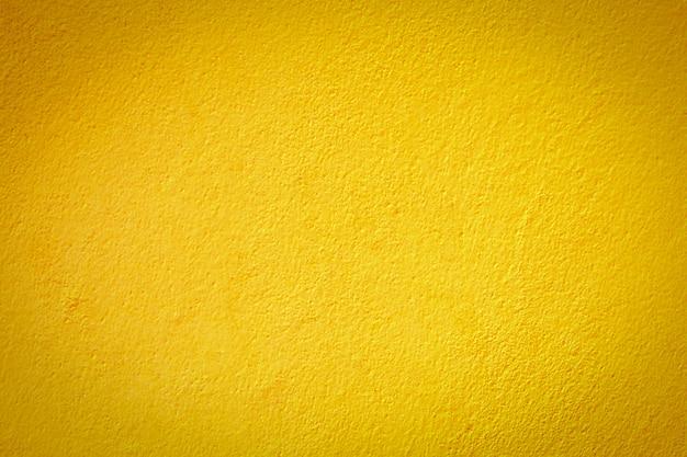 Fondo hermoso de la textura de la pared del cemento amarillo.