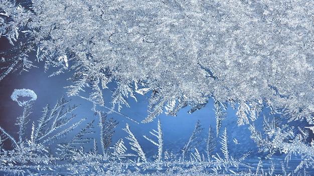 Fondo de hielo abstracto, fondo azul con grietas en la superficie del hielo. patrón escarchado en el cristal de la ventana de invierno