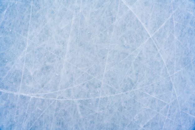 Fondo de hielo con marcas de patinaje y hockey, textura azul de la superficie de la pista con arañazos