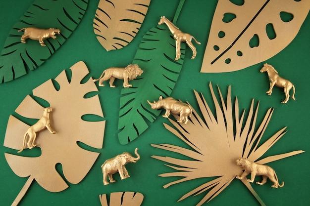 Fondo con hojas doradas tropicales y animales exóticos.