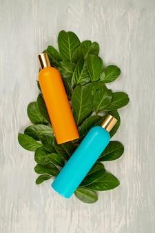 Fondo con hojas verdes y plantas y botella de cosmético. concepto de cuidado natural de scin