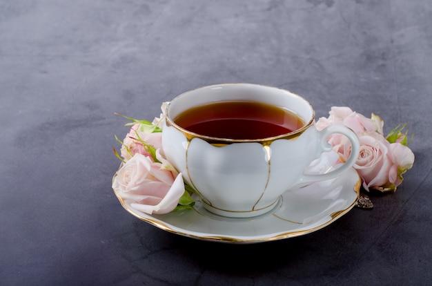 Fondo de la hora del té con una taza de té de porcelana blanca vintage, rosas rosadas suaves