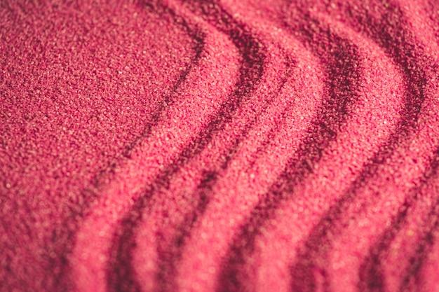 Un fondo horizontal de arena rosa.