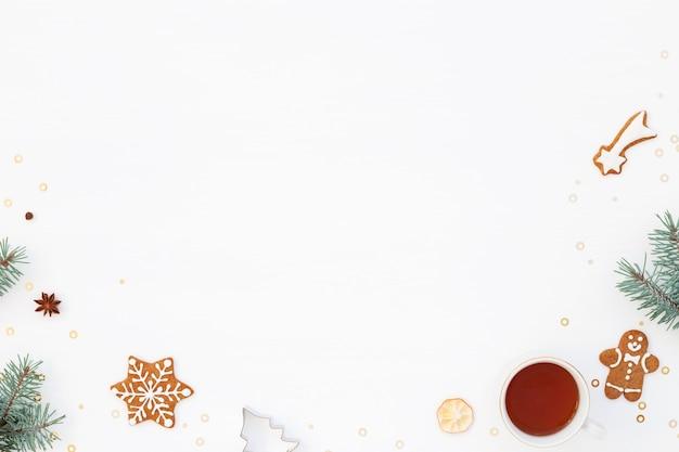 Fondo de humor navideño con pan de jengibre, taza de té y árbol verde