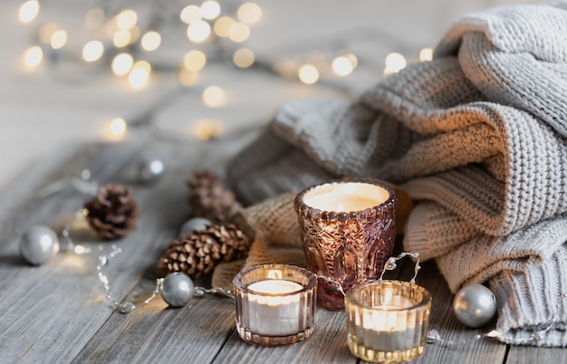 Fondo de invierno acogedor con velas encendidas, detalles decorativos, elementos tejidos con luces bokeh, espacio de copia.