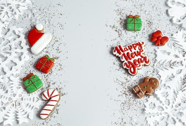 Fondo de invierno decorado con glaseado de pan de jengibre, copos de nieve y confeti vista superior. feliz año nuevo
